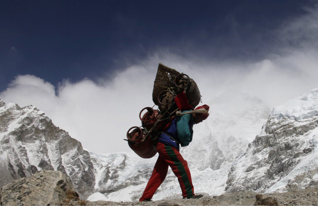 A Nepalese porter walks with his load from Everest base camp in Nepal, May 03, 2011. Porters walk for weeks, sometimes carrying supplies heavier than their own body weight. They do not sit down when they rest but rely on the wooden staff to prop up the baskets. Picture taken May 03, 2011. REUTERS/Laurence Tan (NEPAL - Tags: SOCIETY TRAVEL) - RTR2MVKN